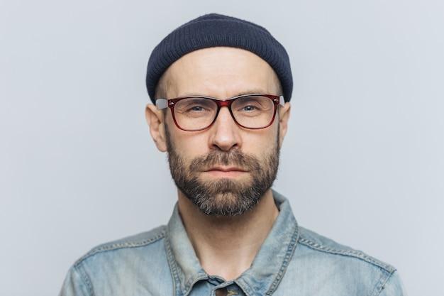 Zdjęcie inteligentnego, stylowego mężczyzny z ciemną, gęstą brodą i wąsami wygląda poważnie