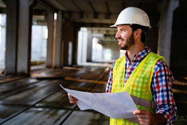 Zdjęcie inżyniera budowy, architekta patrzącego na plan