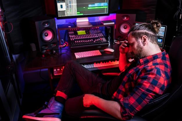 Zdjęcie inżyniera dźwięku pracującego w studiu nagrań muzycznych, wykorzystuje płytę mikserską do tworzenia nowoczesnego dźwięku. odnoszący sukcesy artysta muzyk pracujący przy biurku kontrolnym.