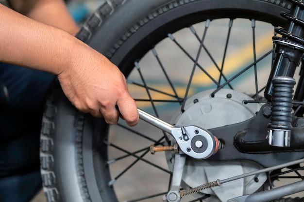 Zdjęcie jest z bliska. ludzie naprawiają motocykl. do pracy użyj klucza i śrubokręta.