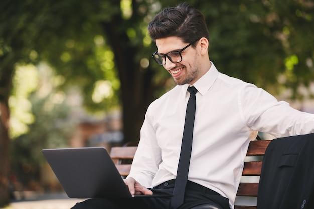 Zdjęcie kaukaski biznesmen w garniturze siedzi na ławce w zielonym parku i pracuje na laptopie w słoneczny dzień
