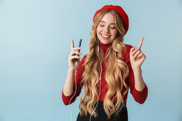 Zdjęcie kaukaski dziewczyna 20s noszenie słuchawek do słuchania muzyki na telefonie komórkowym na białym tle