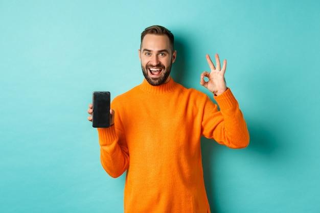 Zdjęcie kaukaskiego mężczyzny pokazującego ekran telefonu komórkowego i znak w porządku, zatwierdzającego sklep internetowy, aplikację na smartfona, stojącego zadowolonego na jasnoniebieskim tle.