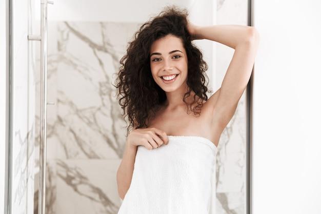 Zdjęcie kaukaskiej kręconej kobiety o długich ciemnych włosach ubrana w biały ręcznik, stojącej w łazience po prysznicu w pokoju hotelowym
