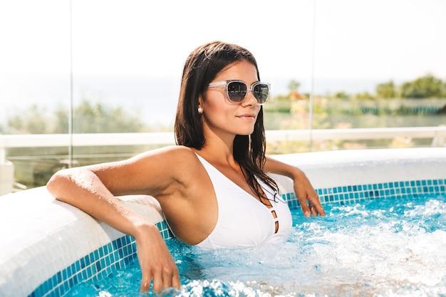 Zdjęcie kaukaskiej wspaniałej kobiety w białym kostiumie kąpielowym i okularach przeciwsłonecznych, siedzącej w basenie, w strefie luksusowych hoteli podczas wakacji