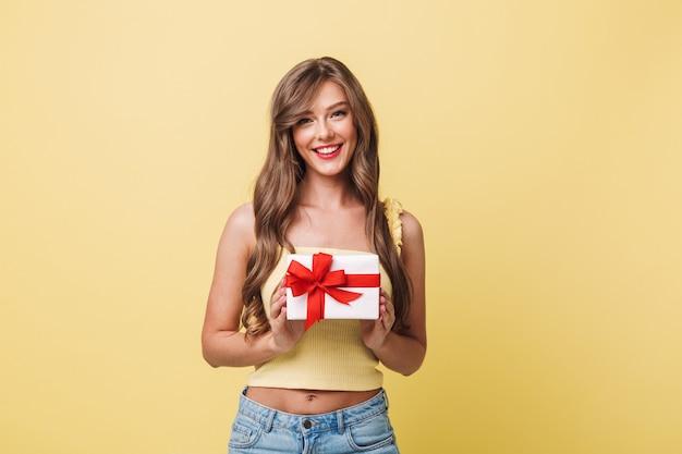 Zdjęcie kaukaskiej zadowolonej kobiety dwudziestki o długich brązowych włosach, uśmiechniętej i trzymającej pudełko owinięte kokardą, odizolowane na żółtym tle