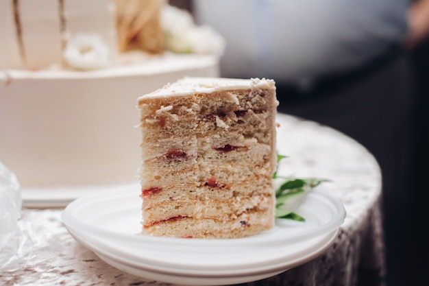 Zdjęcie kawałka pysznego białego tortu weselnego na talerzu