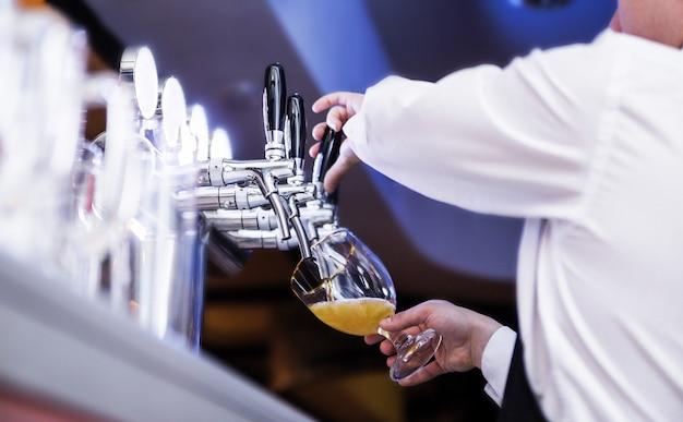 Zdjęcie kelnera nalewa piwo do szklanki