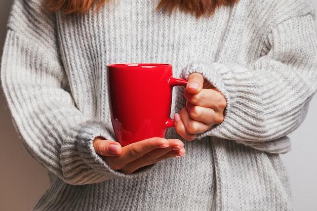 Zdjęcie kobiecej ręki trzymającej czerwony kubek kawy