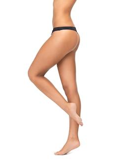 Zdjęcie kobiecych nóg w czarnych majtkach od bikini