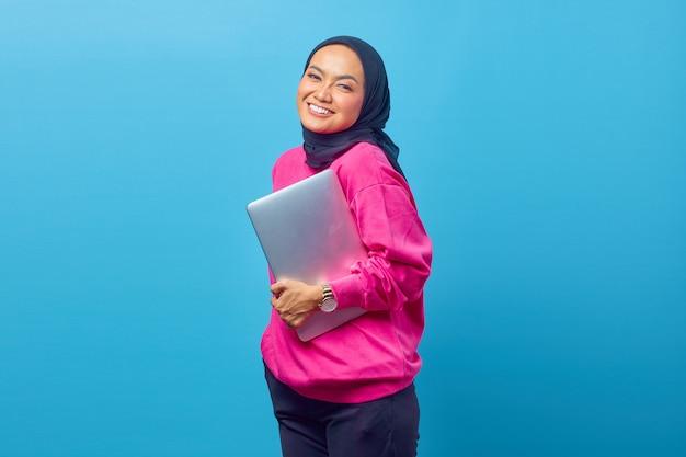 Zdjęcie kobiet asia trzyma laptop nosić różowy sweter na niebieskim tle