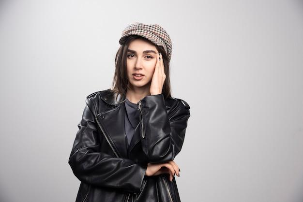 Zdjęcie kobiety dotykającej jej głowy w czarnej skórzanej kurtce i czapce.