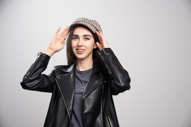 Zdjęcie kobiety pozuje w czarnej skórzanej kurtce i czapce.