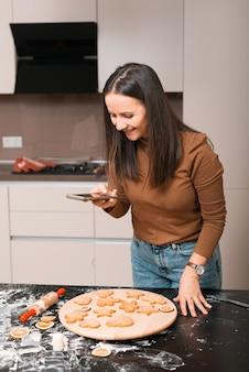 Zdjęcie kobiety stojącej w kuchni i robiącej smartfonem zdjęcie świeżo upieczonych herbatników imbirowych