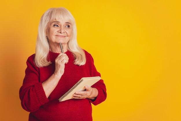 Zdjęcie kobiety trzymającej notatnik na jasnożółtym kolorowym tle