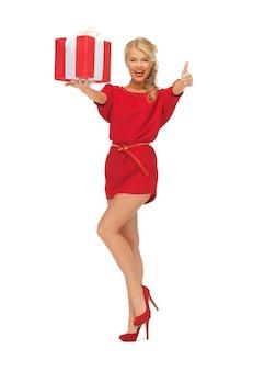Zdjęcie kobiety w czerwonej sukience z pudełkiem na prezent