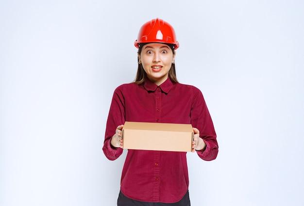 Zdjęcie kobiety w czerwonym kasku trzymając karton na białym tle.