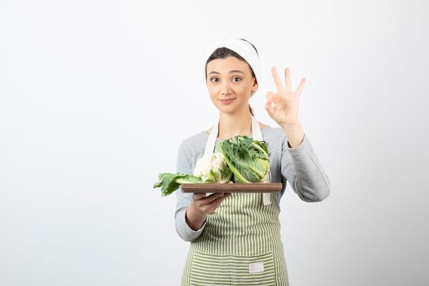 Zdjęcie kobiety w fartuchu z drewnianym talerzem kalafiorów pokazującym ok gest