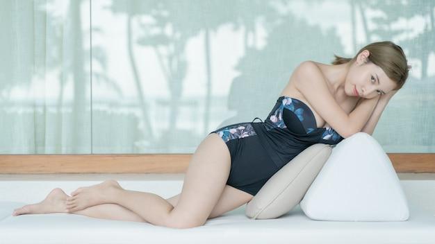 Zdjęcie kobiety w kostiumie kąpielowym opalającej się, leżąc na łóżku w salonie
