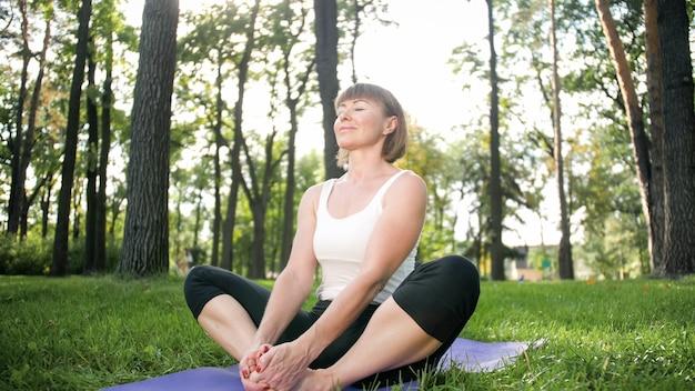 Zdjęcie kobiety w średnim wieku, uśmiechnięta praktykowania asan jogi. osoba medytująca w przyrodzie. równowaga i harmonia ciała i umysłu