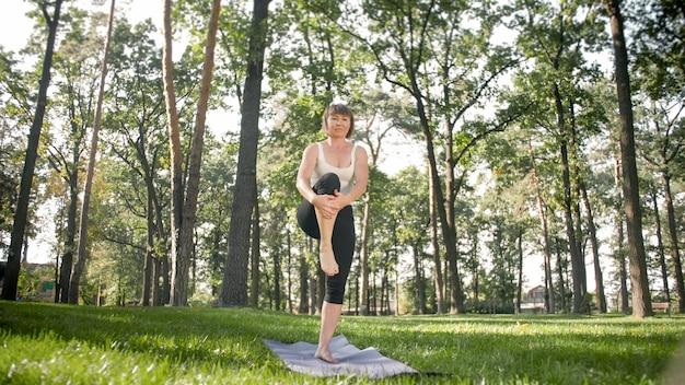 Zdjęcie kobiety w średnim wieku w ubraniach sportowych uprawiania jogi na świeżym powietrzu w parku. kobieta w średnim wieku rozciągająca się i medytująca w lesie