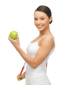 Zdjęcie kobiety z miarką i jabłkiem