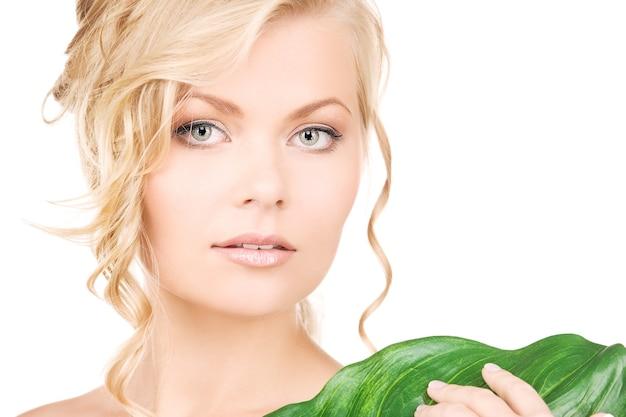 Zdjęcie kobiety z zielonym liściem na białym