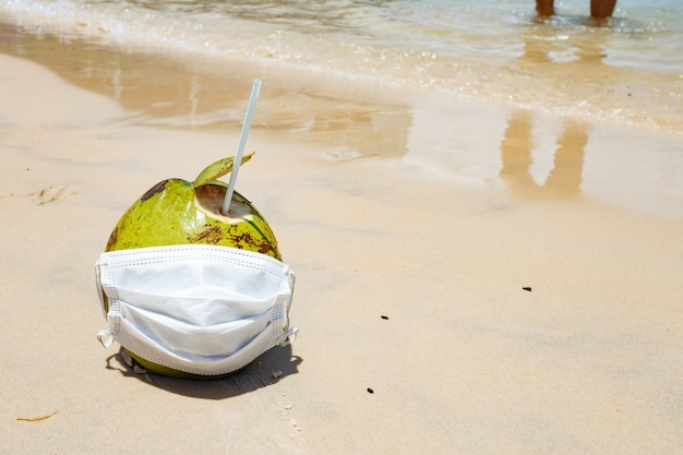 Zdjęcie kokosa na plaży z maską chirurgiczną. koncepcja pandemii i wakacji