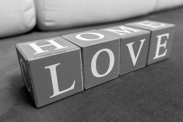 """Zdjęcie koncepcyjne słów """"dom"""" i """"miłość"""" pisanych literami na cegłach"""