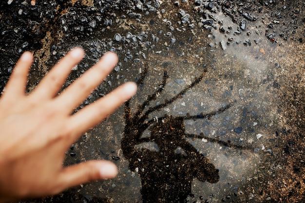 Zdjęcie koncepcyjne. witaj nieznajomy koncepcja. fotograf wykonujący autoportret autorstwa shadow on the ground. dziwna, przerażająca ręka odbija się na podłodze. widok z góry