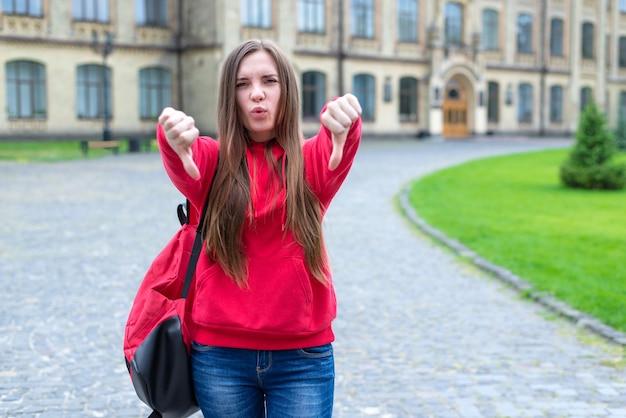 Zdjęcie kpiącego z niezadowolonej nastoletniej hipsterki w swobodnych dżinsach i bluzie ze swetrem, z palcami w dół