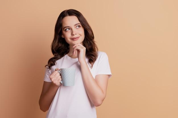 Zdjęcie kreatywnej ślicznej damy wygląda na pustą przestrzeń trzymaj kubek pić kawę pozowanie na beżowym tle