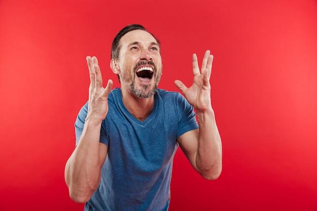 Zdjęcie krzyczącego i radującego się ekstatycznego człowieka z gestem jak zwycięzca lub osoba sukcesu, na białym tle nad czerwonym tle