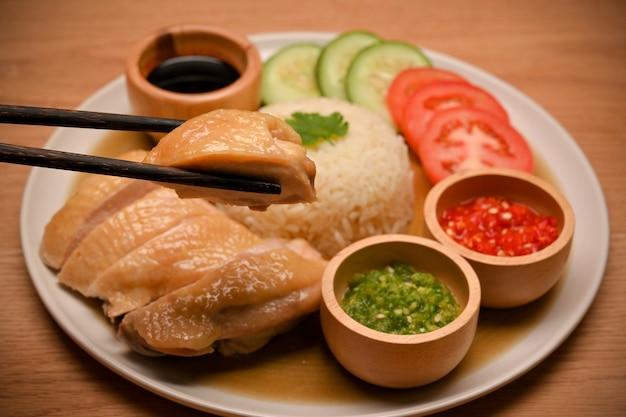 Zdjęcie kuchni azjatyckiej ryż z kurczaka po hajnie podawany z warzywami i specjalnymi sosami na drewnianym stole