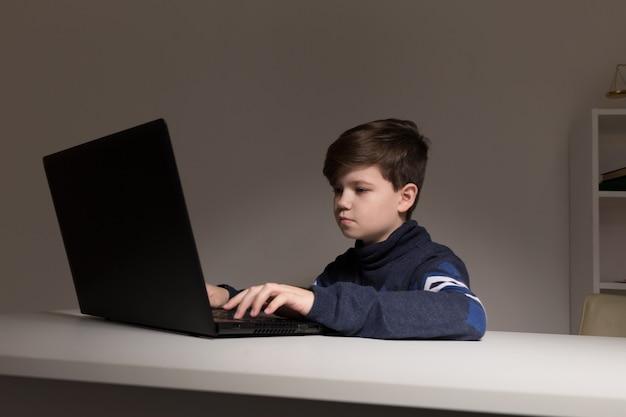 Zdjęcie ładnego chłopca w swetrze siedzi przed komputerem odrabiania lekcji.