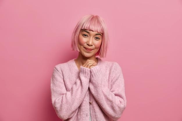 Zdjęcie ładnej azjatki w dobrym humorze, trzyma ręce razem, ma czarująco uśmiechnięty wyraz twarzy, myśli o czymś przyjemnym, nosi różowy sweter, stoi pod dachem.