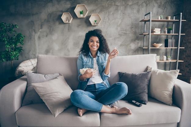 Zdjęcie ładnej ciemnej skóry, falującej pani, domowej roboty, jedzącej popcorn, oglądającej ulubiony humorystyczny program telewizyjny, siedzącej na przytulnej kanapie, swobodny strój dżinsowy płaski w pomieszczeniu