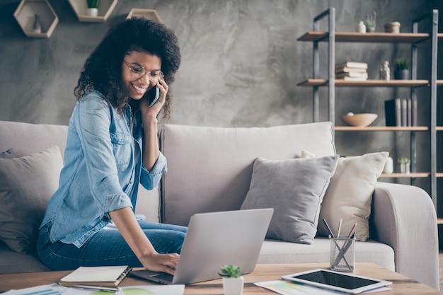 Zdjęcie ładnej ciemnej skóry kręconej biznesowej pani przeglądającej notebook na stole rozmawiającej przez telefon koledzy partnerzy siedzący przytulna kanapa nosić specyfikacje swobodny dżinsowy strój mieszkanie w pomieszczeniu