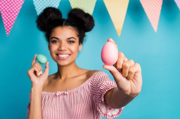 Zdjęcie ładnej ciemnoskórej pani pokazującej świąteczne pomalowane jajka kolorowe dekoracje flagi porady wybierz różowe jajko nosić czerwoną białą koszulę w paski nagie ramiona odizolowane niebieski kolor rozmyta ściana