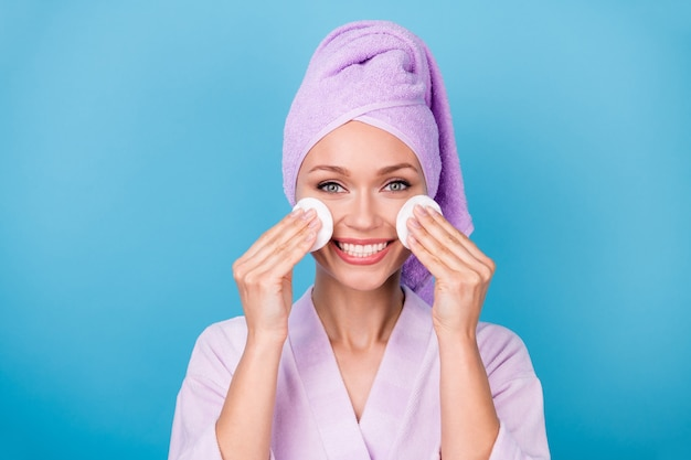 Zdjęcie ładnej dziewczyny podnosi dwie ręce trzymaj bawełniane dyski twarz nosić fioletowy ręcznik turban szlafrok na białym tle niebieski kolor tła