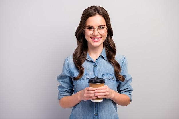 Zdjęcie ładnej freelancerki pani trzymaj kubek papierowy gorąca kawa napój przerwa proces pracy nosić specyfikacje na co dzień dżinsy koszula dżinsowa na białym tle szary kolor