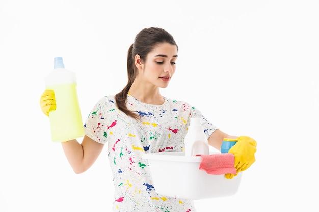 Zdjęcie ładnej gospodyni domowej w wieku 20 lat w żółtych gumowych rękawiczkach do ochrony rąk, trzymająca wiadro ze środkami czyszczącymi na białym tle nad białą ścianą