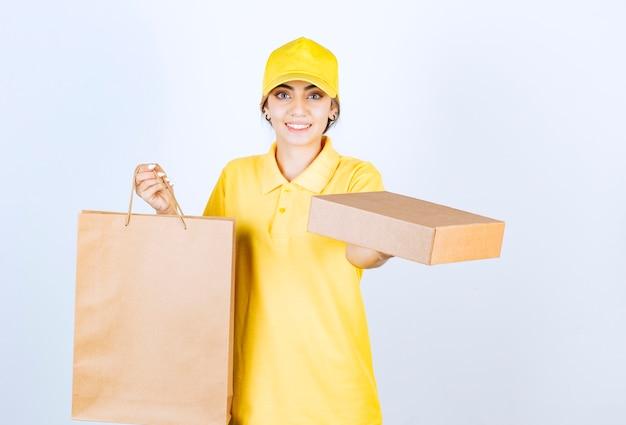 Zdjęcie ładnej kobiety w żółtym mundurze trzymającej brązowe puste pudełko papierowe i torbę.
