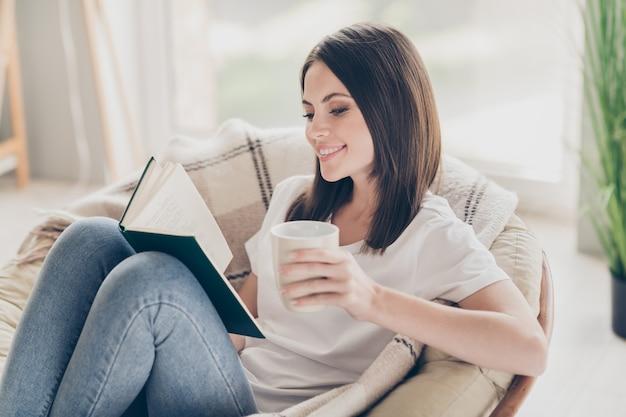 Zdjęcie ładnej młodej dziewczyny siedzi na krześle czytać ciekawą książkę trzymać filiżankę herbaty nosić dżinsy w domu w domu