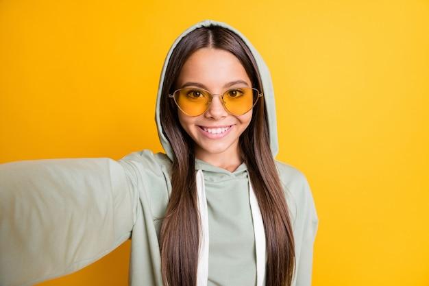 Zdjęcie ładnej młodej dziewczyny uśmiech sprawia, że zdjęcie nosi kaptur jasne okulary przeciwsłoneczne na żywym żółtym kolorze tła