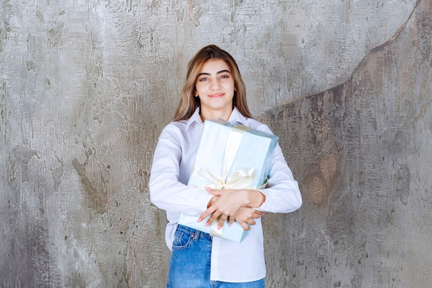 Zdjęcie ładnej modelki z długimi włosami trzymającej duży prezent