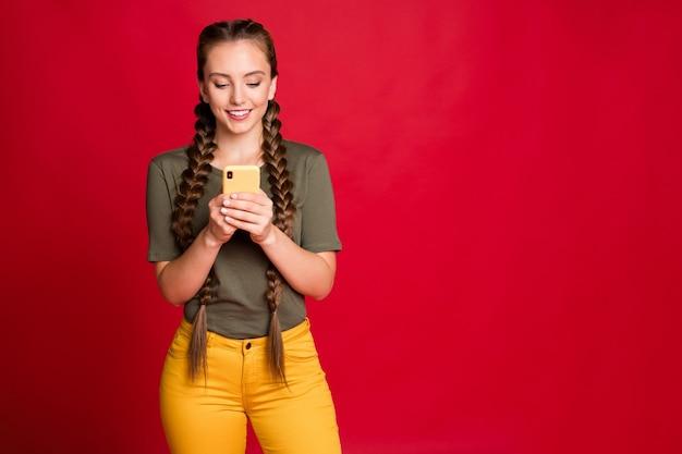 Zdjęcie ładnej pani długie warkocze trzymające telefon za ręce czytające nowe pozytywne komentarze zainteresowane ubranie dorywczo żółte spodnie zielona koszulka na białym tle czerwony kolor tło