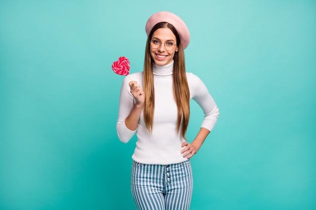 Zdjęcie ładnej pani podróżnik trzymać duży cukierek na patyku czerwone serce rysunek ząb uśmiechnięty dobry nastrój nosić specyfikacje różowy beret biały golf paski dżinsy na białym tle turkusowy kolor tła