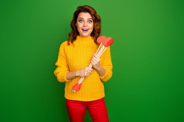 Zdjęcie ładnej pani trzymaj amorek miłość strzały gotowe strzelać celuje ekscytujące hobby impreza tematyczna nosić żółty sweter z dzianiny czerwone spodnie odizolowany zielony kolor ściana