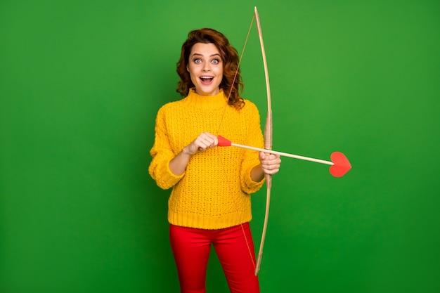 Zdjęcie ładnej pani trzymaj amorek miłość strzały łuk strzelać celowanie kochające serca motyw party postać nosić żółty sweter z dzianiny czerwone spodnie na białym tle zielony kolor ściana